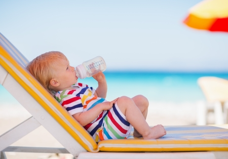 Portrait of baby on sunbed drinking water photo