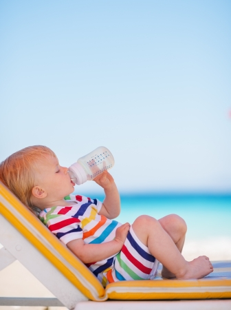 beach drink: Portrait of baby on sun bed drinking water Stock Photo