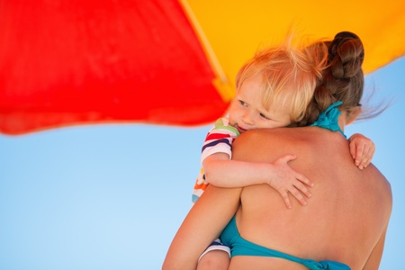 Baby embracing mother on beach under umbrella Stock Photo - 14246463