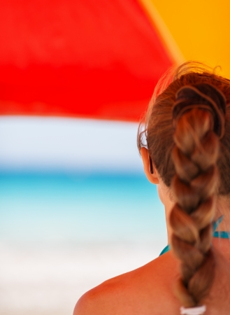 Woman on beach under umbrella looking into distance. Rear view Stock Photo - 14246413
