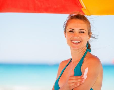 Happy woman applying sun block creme on arm photo