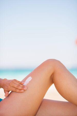 Closeup on female hand applying sun block creme on leg photo