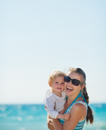 Portrait of happy mother and baby on beach photo