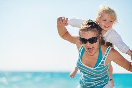 Baby piggybacking mother on beach photo