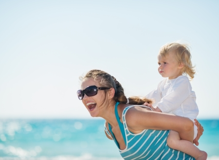 Kid piggybacking mother on beach photo