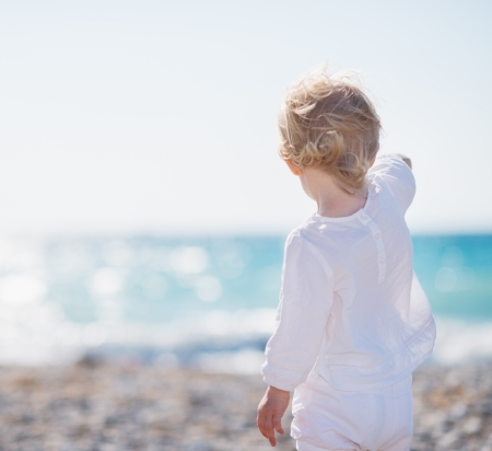 Baby on beach pointing into distance Stock Photo - 14246349