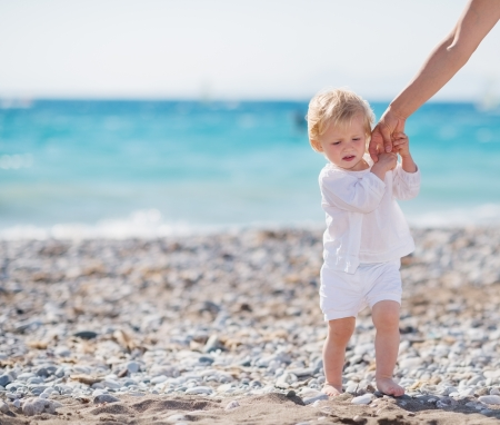 Baby holding mothers hand and walking on beach photo
