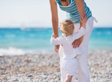 Baby on beach climbing mothers hands Stock Photo - 14246442