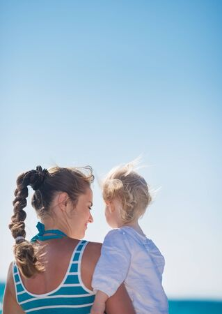 Portrait of mother and baby on beach. Rear view Stock Photo - 14246404