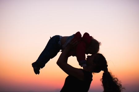 Silhouette of mother playing with baby in dusk photo