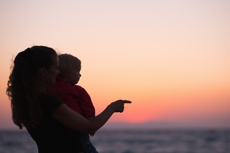 Silhouette of mother with baby in sunset pointing on copy space photo