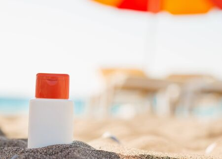 Bottle of sun block creme in shadow on beach Stock Photo - 14250364