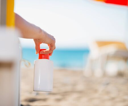 Closeup on bottle of sun block creme in female hand Stock Photo - 14250371