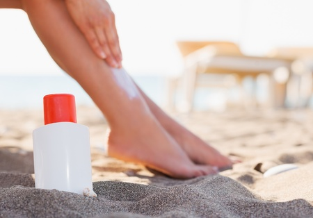 suntan lotion: Bottle of sun block and female applying creme on leg on beach