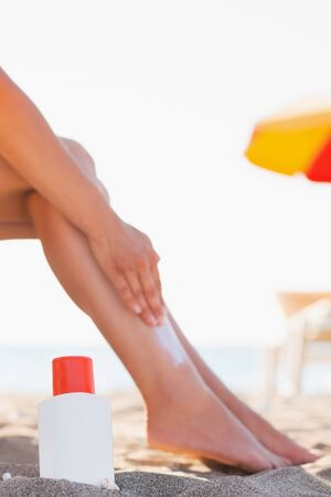 Bottle of sun block and female applying creme on leg on beach Stock Photo - 14250357