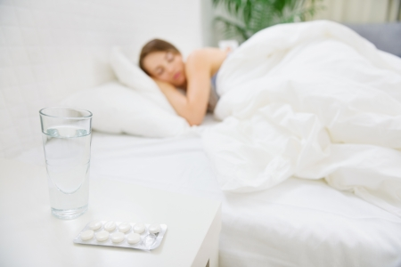 Glass of water and pack of pills on table and woman sleeping in background Stock Photo - 14246328