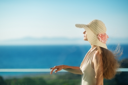 Woman looking on sea from balcony. Rear view Stock Photo