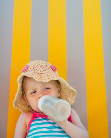 Baby laying on sun bed and drinking from bottle Stock Photo - 14329476