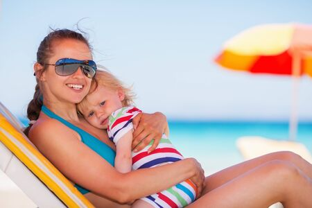 Happy mother laying on sun bed and hugging baby Stock Photo - 14329465