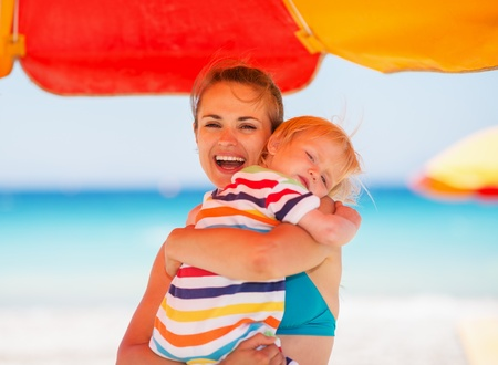 Mother embracing baby on beach under umbrella Stock Photo - 14329453