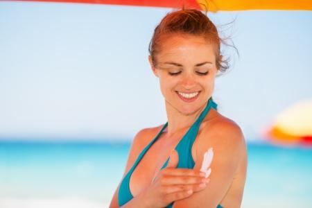 Happy woman applying sun screen creme on arm photo