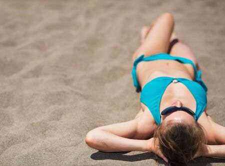 Woman laying on sand beach. Rear view photo