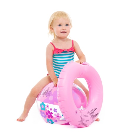 Baby girl in swimsuit with inflatable ring sitting on ball Stock Photo