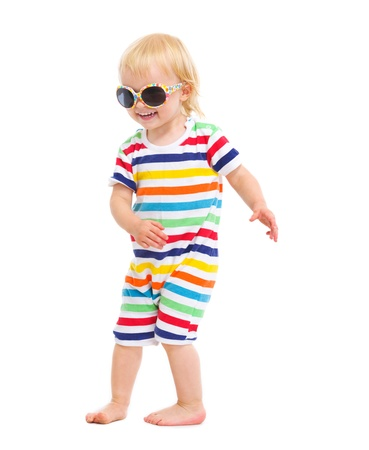 baby in suit: Happy baby in swimsuit and sunglasses dancing Stock Photo