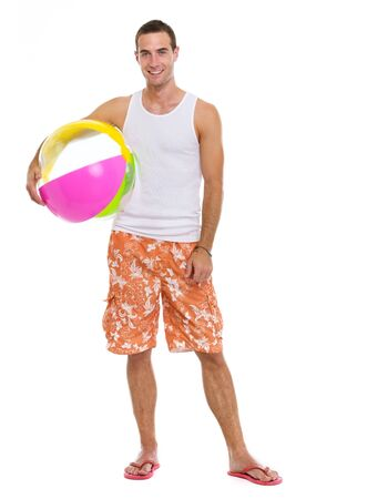 Resting on vacation smiling young man with beach ball photo