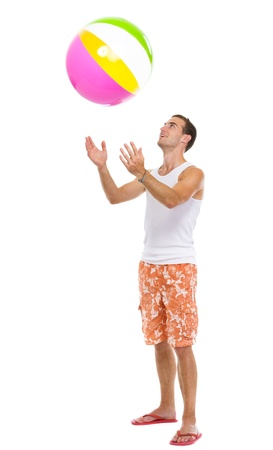 Resting on vacation happy young man throwing beach ball up photo
