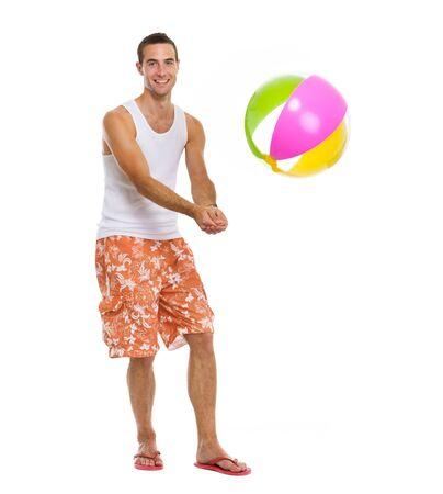 balon voleibol: En vacaciones feliz hombre joven que juega al voleibol con pelota de playa Foto de archivo