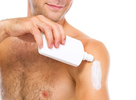 Closeup on man applying sun block creme on arm Stock Photo