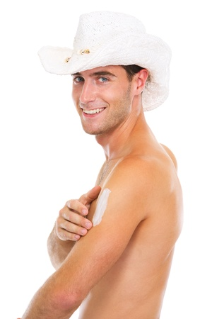sun lotion: Smiling guy in hat applying sun block creme on arm Stock Photo