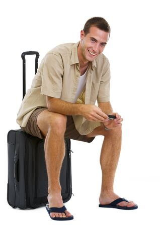 Happy tourist sitting on wheels bag and waiting for airplane photo