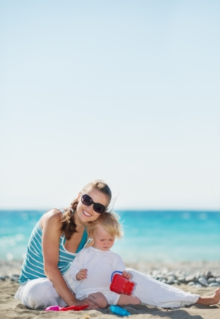 Happy mother and baby playing on beach photo
