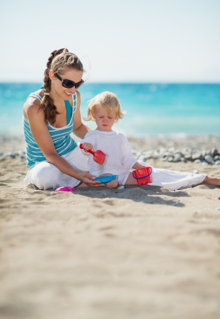 Mother and baby playing with sand on beach Stock Photo - 14454329