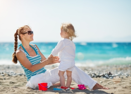 Mother playing with baby on beach photo