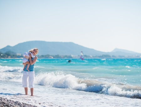 Baby hugging mother standing at sea shore Stock Photo - 14454319