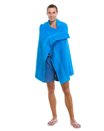 Happy young man wrapped in blue beach towel photo
