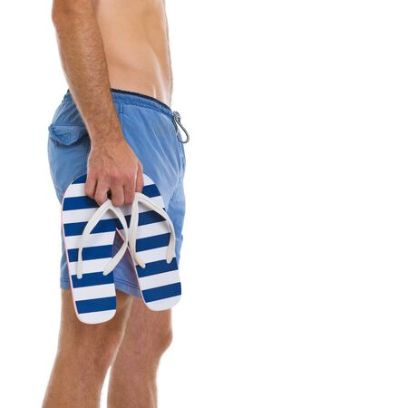 Closeup on young man holding flip flops Stock Photo - 14555162
