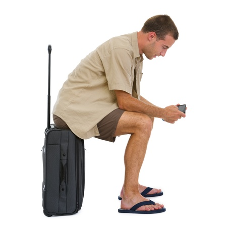 Tourist sitting on bag and checking vacation photos while waiting airplane Stock Photo - 14529597