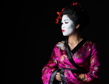 Portrait of geisha looking on copy space isolated on black photo