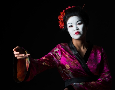 Portrait of geisha showing on something isolated on black