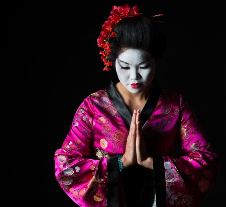 Portrait of geisha with hands together respect gesture isolated on black photo