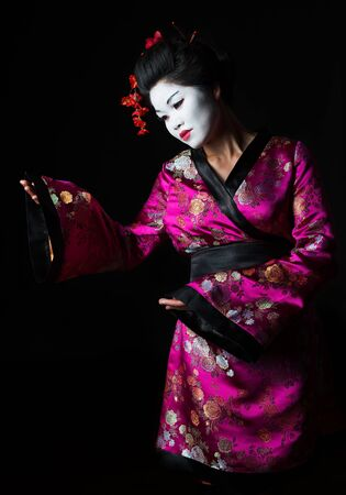 Portrait of geisha presenting something isolated on black Stock Photo - 14596596