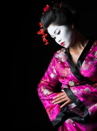 Closeup portrait of geisha isolated on black photo