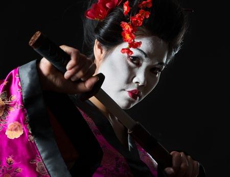 Portrait of geisha pulls out sword of sheath on black photo