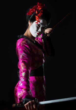 Portrait of geisha holding sword isolated on black photo