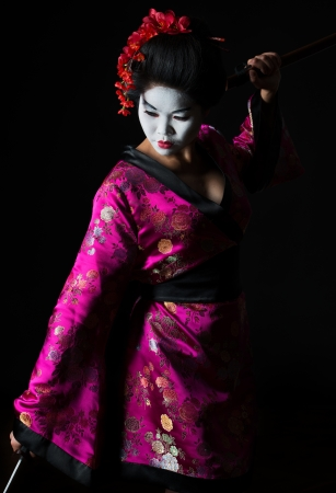 Portrait of geisha dancing with sword isolated on black photo