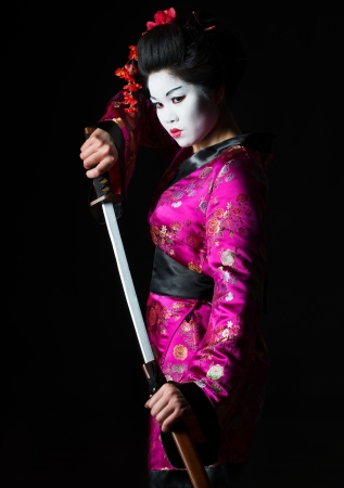 Portrait of geisha warrior pulls out sword of sheath on black photo